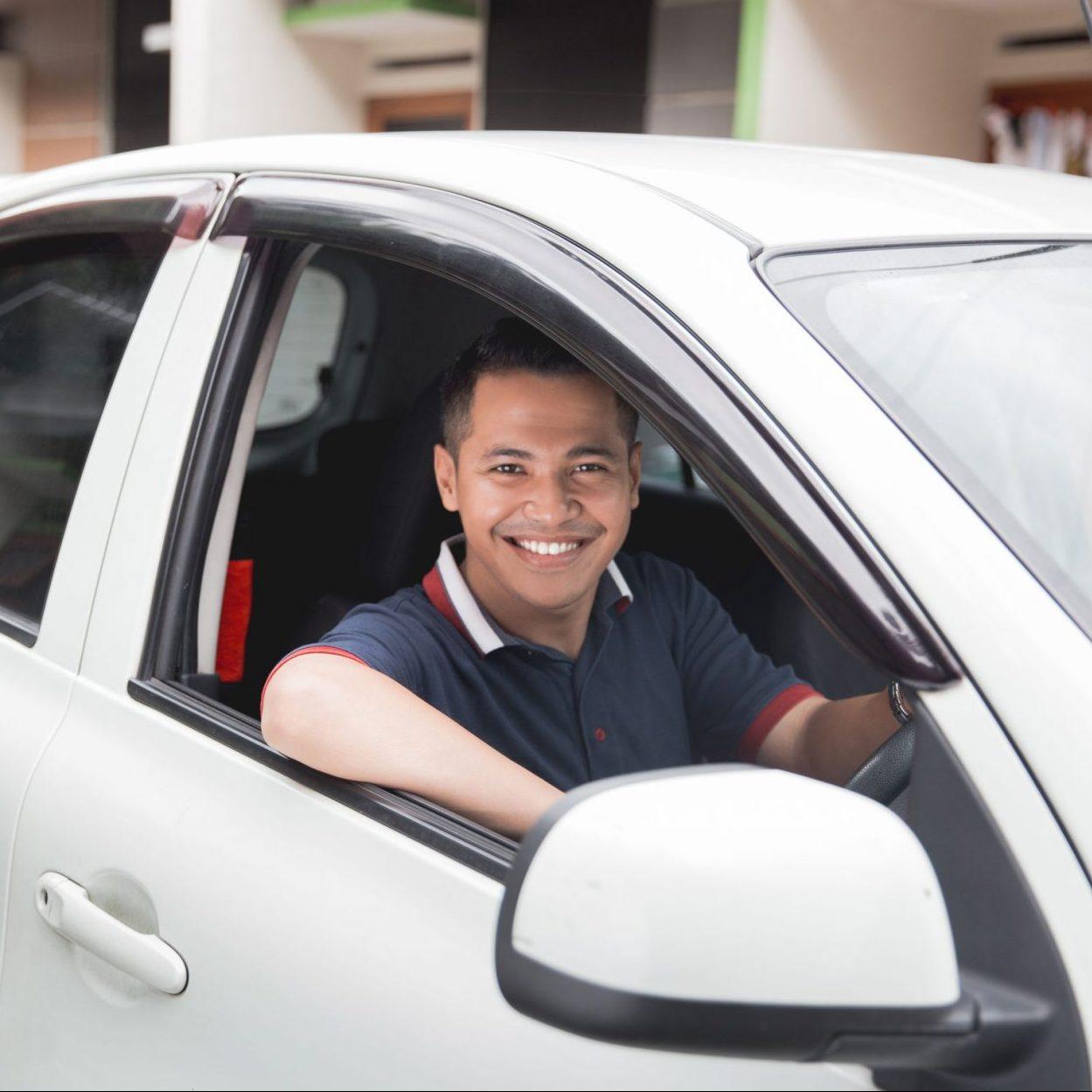 happy young asian driver smiling to camera
